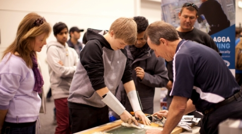 A young person being shown how to screenprint.