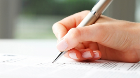 Close up of a pen and hand writing on a document.