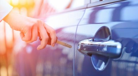 A hand inserts a car key into a car door's lock.