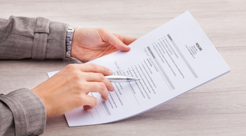 Hand holding a resume at a desk