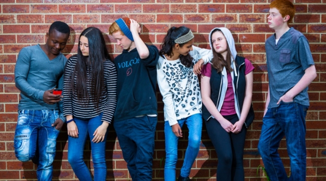 Six teenagers leaning against a brick wall.