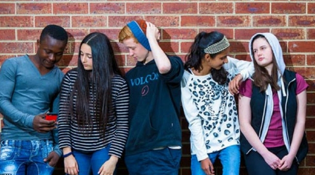 Group of young people standing against a brick wall.